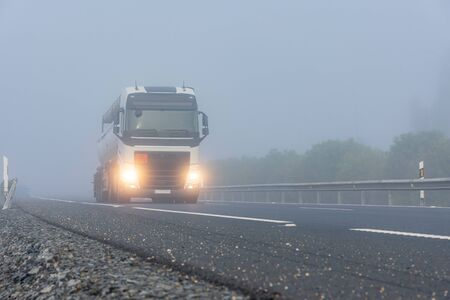 Tank truck with dangerous goods circulating on the highway on a day of thick fog. Stock Photo