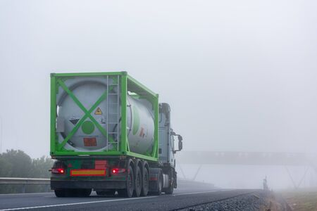 Truck transporting container with dangerous goods circulating on a highway with dense fog