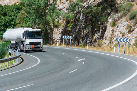 Fuel tank truck driving around a curve in the road