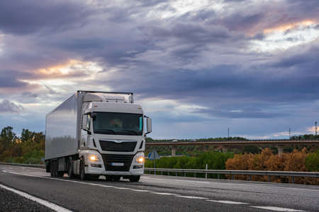 Refrigerated semi-trailer truck driving on a highway under a dramatic sunset sky.
