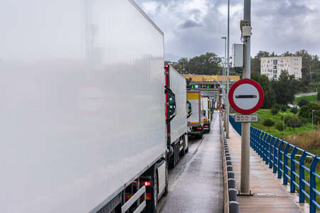Customs or next border sign next to a line of trucks waiting to cross. Stock Photo