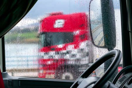 View from inside a truck on a rainy day, with another red truck passing by. Imagens