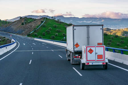 Truck with a small trailer, with panels of dangerous goods for transport of explosives, circulating on the highway. Banque d'images