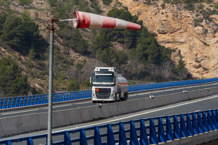 Tank truck with dangerous goods circulating through a viaduct and an windsock indicating that there is a strong wind.