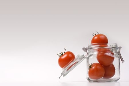 Tomatoes in a jar isolated on white