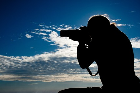 Teenager photographer sihlouette on blue sky Stock Photo