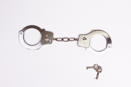 a pair of handcuffs with keys, isolated photo