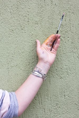 Painter holding brush against a green wall photo