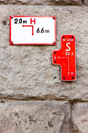Various utilities signs on rock wall photo