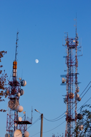 Various gsm and radio antenna against blue sky