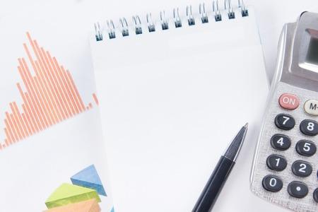 contabilidad financiera cuentas: Concepto de las finanzas - Contabilidad financiera an�lisis gr�ficos de la bolsa. Calculadora, bloc de notas con la hoja de papel en blanco, pluma en la carta. Vista superior. Foto de archivo