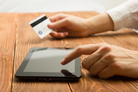 web shopping: Hands holding credit card typing numbers on tablet pc making online payment at home at the wooden table. Online shopping concept. Selective focus