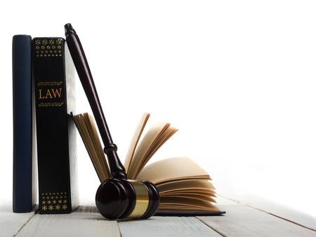 法の概念 - 白い背景に分離された法廷または法律の施行オフィスでテーブルの木製裁判官小槌を持ったオープン法の本。テキストのためのスペース 写真素材