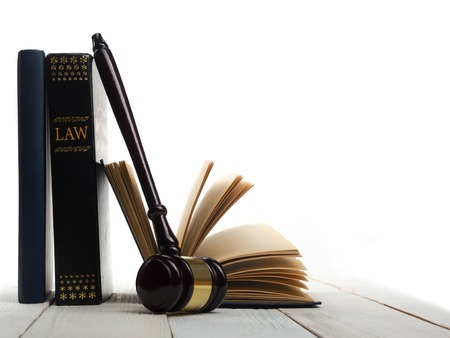 Law concept - Open law book with a wooden judges gavel on table in a courtroom or law enforcement office isolated on white background. Copy space for text. Stock Photo