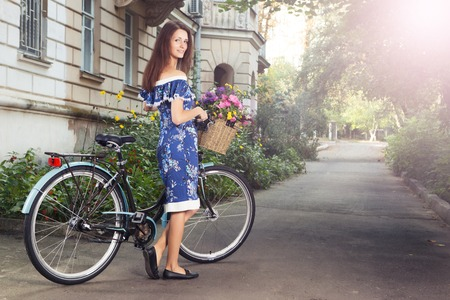 cruiser bike: Portrait of a happy beautiful young girl with vintage bicycle and flowers on city background in the sunlight outdoor. Cruiser with basket full of flowers. Active Leisure Concept