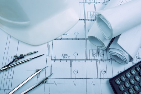 architectural plan: Architectural blueprints, blueprint rolls, compass divider, calculator, white safety on graph paper. Engineering tools view from the top. Copy space. Construction background