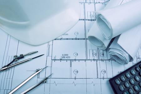 planos arquitectónicos, rollos de blueprint, divisor del compás, calculadora, blanco de seguridad en papel cuadriculado. herramientas de ingeniería vista desde la cima. Copiar el espacio. fondo de la construcción