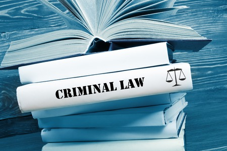 international criminal court: Law concept - Law book with Criminal Law  word on table in a courtroom or law enforcement office. Toned image. Stock Photo