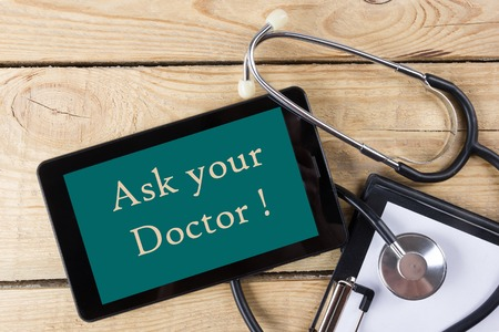 medical person: Ask your Doctor   - Workplace of a doctor. Tablet, stethoscope, clipboard on wooden desk background. Top view.