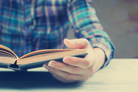 Closeup hand open book for reading concept background. Toned image