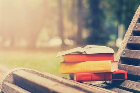 Stapel hardback boeken en Open boek liggend op de bank bij zonsondergang park tegen onscherpe aard achtergrond. Exemplaar ruimte, terug naar school. Onderwijs achtergrond. Gestemd beeld.