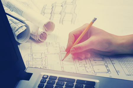 engineering plans: Architect working on blueprint. Architects workplace - architectural project, blueprints, ruler, calculator, laptop and divider compass. Construction concept. Engineering tools. Toned image. Stock Photo
