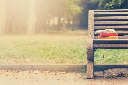 Pila de libros de tapa dura y libro abierto que miente en banco en el parque de la puesta del sol contra la naturaleza telón de fondo difuminado. Espacio en blanco, de vuelta a la escuela. Antecedentes educacionales. la imagen en tonos.