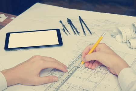architect tools: Architect working on blueprint. Architects workplace - architectural project, blueprints, ruler, calculator, laptop and divider compass. Construction concept. Engineering tools. Toned image. Stock Photo