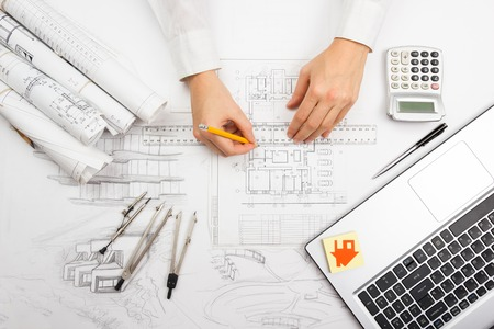 engineering plans: Architect working on blueprint. Architects workplace - architectural project, blueprints, ruler, calculator, laptop and divider compass. Construction concept. Engineering tools.