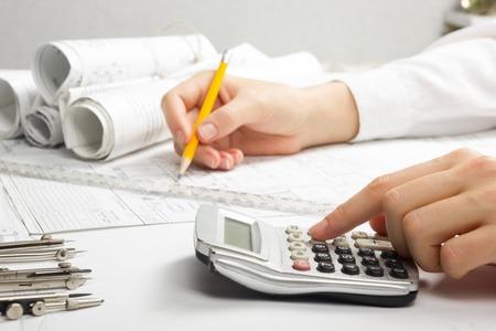Architekt pracuje na návrhu. Architekti pracoviště - architektonického projektu, modrotisků, pravítko, kalkulačka, notebook a dělič kompas. Koncepce stavby. Inženýrské nástroje. Reklamní fotografie