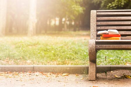 banc de parc: Pile de livres cartonnés et livre ouvert couché sur un banc de parc au coucher du soleil contre nature floue toile de fond. Copier l'espace, de retour à l'école. Education fond Banque d'images
