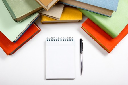 Stack of colorful books, notebook with blank sheet of paper and pen on wooden table. Back to school. Copy space.