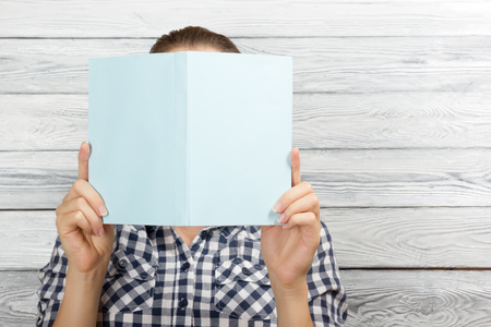 woman hiding: Woman reading a book and covering her face over wooden background.
