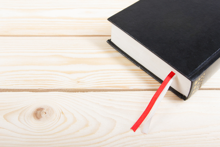 a study: Black book with red and white bookmark on wooden table. Back to school. Copy space. Stock Photo