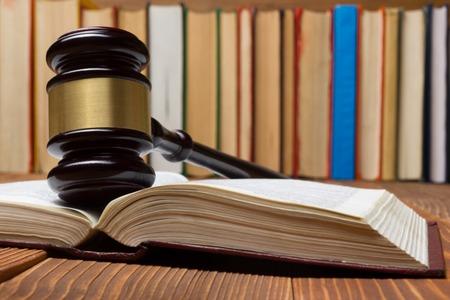 Law concept - Gesetzbuch mit einem hölzernen Richter Hammer auf dem Tisch in einem Gerichtssaal oder Strafverfolgungs Büro