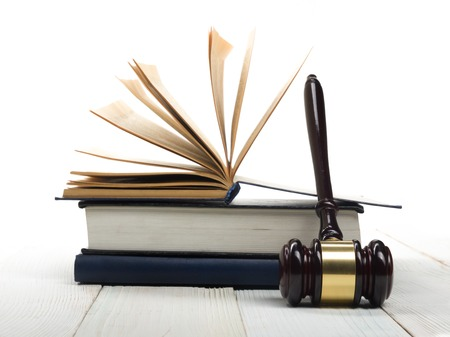 criminal case: Law concept - Open law book with a wooden judges gavel on table in a courtroom or law enforcement office isolated on white background. Copy space for text. Stock Photo