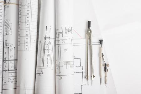 Lugar de trabajo del arquitecto - Proyecto de arquitectura, planos, rodillos y la tableta, el lápiz, compás divisor de planes. herramientas de ingeniería vista desde la cima. Fondo de la construcción. Espacio en blanco para el texto