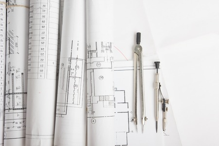 engineering plans: Workplace of architect - Architectural project, blueprints, rolls and tablet, pen, divider compass on plans. Engineering tools view from the top. Construction background. Copy space for text
