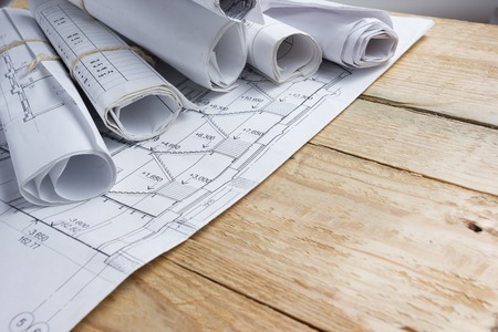 Architectural project, blueprints, blueprint rolls and divider compass, calipers on vintage wooden background. Construction concept. Engineering tools. Copy space.
