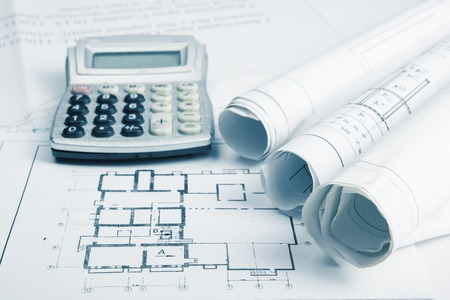 architecture: Workplace of architect - Architectural project, blueprints, rolls and calculator on plans. Engineering tools view from the top. Construction background. Copy space for text Stock Photo