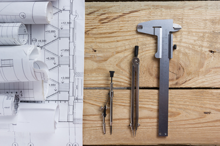 calipers: Architectural project, blueprints, blueprint rolls and divider compass, calipers on vintage wooden background. Construction concept. Engineering tools. Copy space.