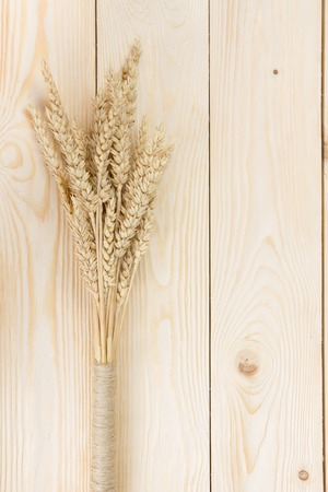 natural backgrounds: Wheat Ears on Wooden Table. Sheaf of Wheat over Wood Background. Harvest concept. Top view. Stock Photo