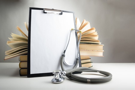 Open hardback books on the table, medical clipboard with blank paper or document, report and stethoscope. Medical professional education and information concept. Back to school, copy space.