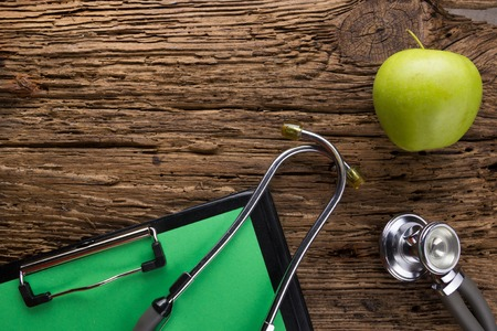 Alternative medicine - stethoscope, clipboard and green apple on wood table top view . Medical background. Concept for diet, healthcare, nutrition or medical insurance.
