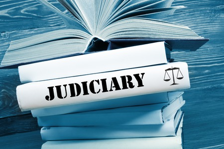 judiciary: Law concept - Law book with Judiciary  word on table in a courtroom or law enforcement office. Toned image.
