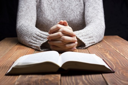 christian women: Woman hands praying with a bible in a dark over wooden table. Stock Photo