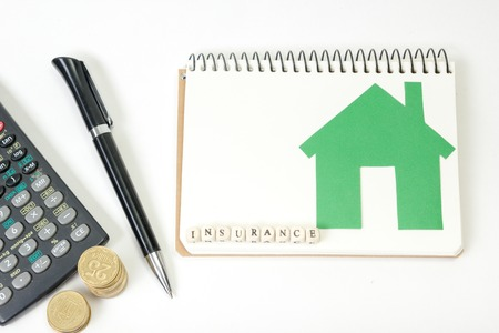 household insurance: Concept of housing purchase and insurance. Office desk table with supplies top view. Calculator. golden coins, pen, notepad, green model house, wooden block with word Insurance.