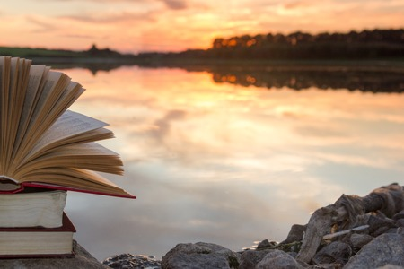 Stack of books and Open hardback book on blurred nature landscape backdrop against sunset sky with back light. Copy space, back to school. Education background Stock Photo
