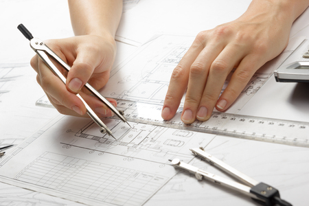 real estate background: Architect working on blueprint. Architects workplace - architectural project, blueprints, ruler, calculator, laptop and divider compass. Construction concept. Engineering tools.