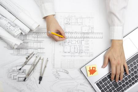 pravítko: Architekt pracuje na návrhu. Architekti pracoviště - architektonického projektu, modrotisků, pravítko, kalkulačka, notebook a dělič kompas. Koncepce stavby. Inženýrské nástroje. Reklamní fotografie
